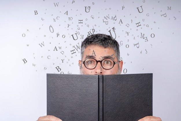 Mann mit den gläsern, die ein notizbuch mit buchstaben in der luft halten