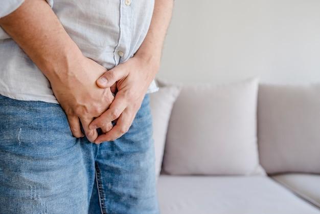 Mann mit den händen, die seine gabelung halten, will er pinkeln - urinausscheidendes inkontinenzkonzept