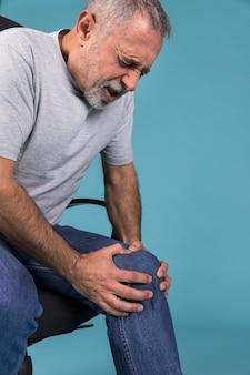 Mann mit den knieschmerz, die auf stuhl sitzen