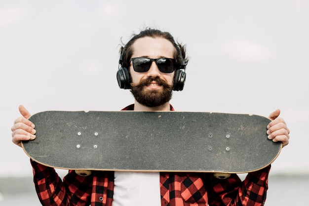 Mann mit den kopfhörern, die skateboard halten
