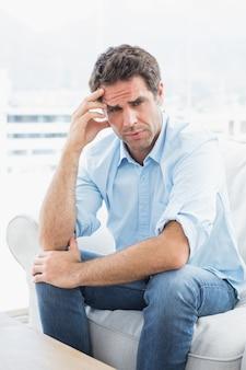 Mann mit den kopfschmerzen, die auf der couch betrachtet kamera sitzen