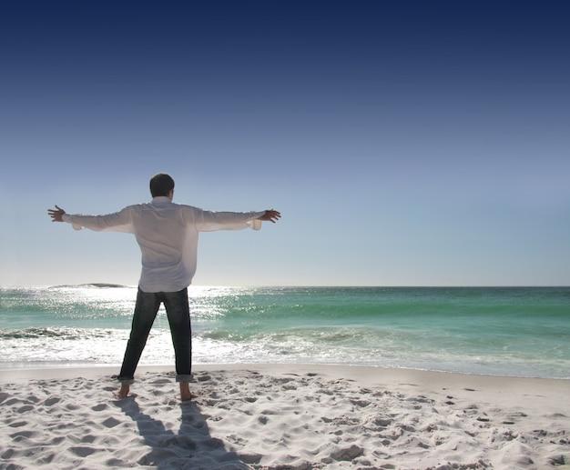 Mann mit den offenen armen, die meer gegenüberstellen
