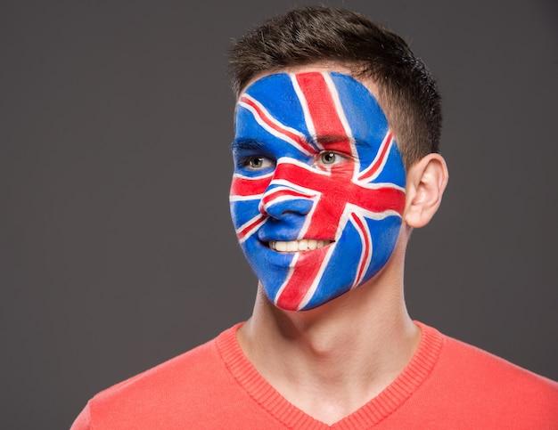 Mann mit der flagge gemalt auf gesicht, um britische unterstützung im sport zu zeigen.