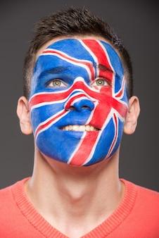 Mann mit der flagge gemalt auf seinem gesicht, um großbritannien zu zeigen.