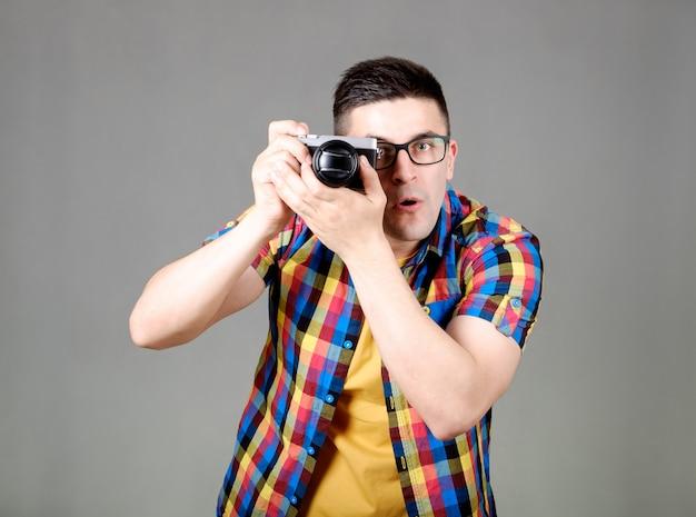 Mann mit der fotokamera lokalisiert auf grauer wand