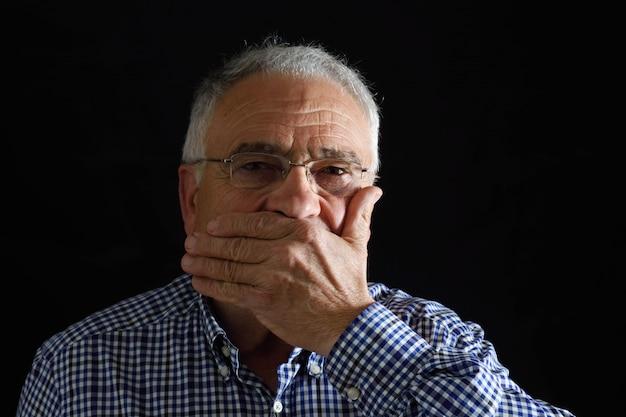 Mann mit der hand im mund auf schwarzem