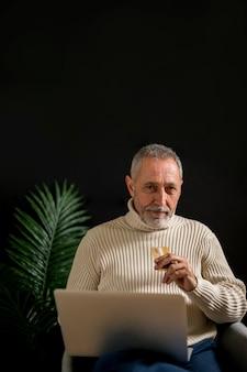 Mann mit der kreditkarte und laptop, die kamera betrachten