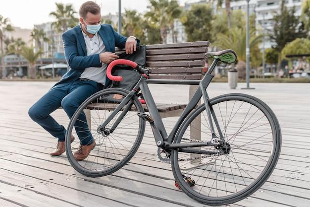 Mann mit der medizinischen maske, die auf einer bank neben seinem fahrrad sitzt