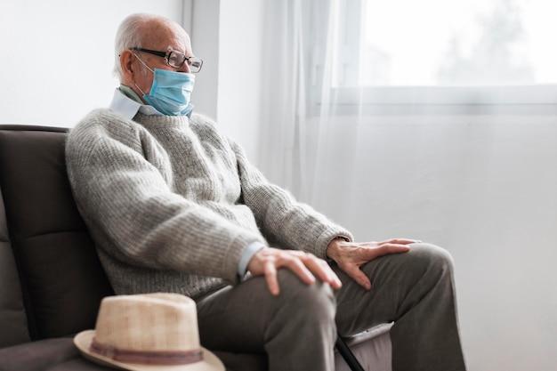 Mann mit der medizinischen maske, die in einem pflegeheim sitzt