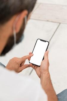 Mann mit der medizinischen maske, die smartphone draußen hält