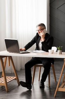 Mann mit der schwarzen jacke, die am schreibtisch sitzt