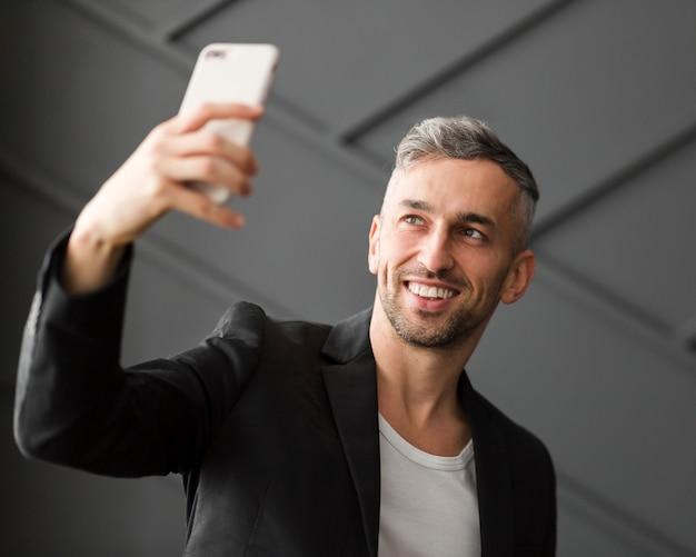 Mann mit der schwarzen jacke, die ein selfie nimmt