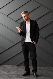 Mann mit der schwarzen jacke, die sein telefon steht und verwendet