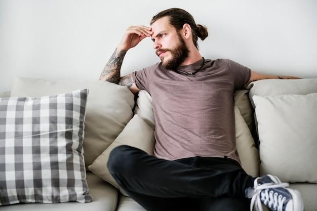 Mann mit der tätowierung, die auf einer couch sitzt