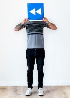 Mann mit der tätowierung, die rückständige ikone hält