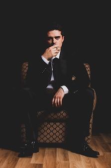 Mann mit der zigarette, die im weinleselehnsessel sitzt
