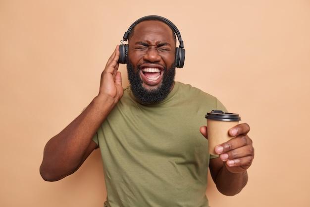 Mann mit dickem bart fühlt sich energetisiert hört tonspur über kopfhörer hält pappbecher kaffee genießt die freizeit lässig gekleidet auf beige
