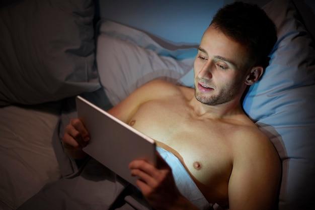 Mann mit digitalem tablet vor dem schlafen