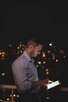 Mann mit digitaler tablette auf dem balkon
