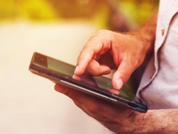 Mann mit digitaler tablette draußen