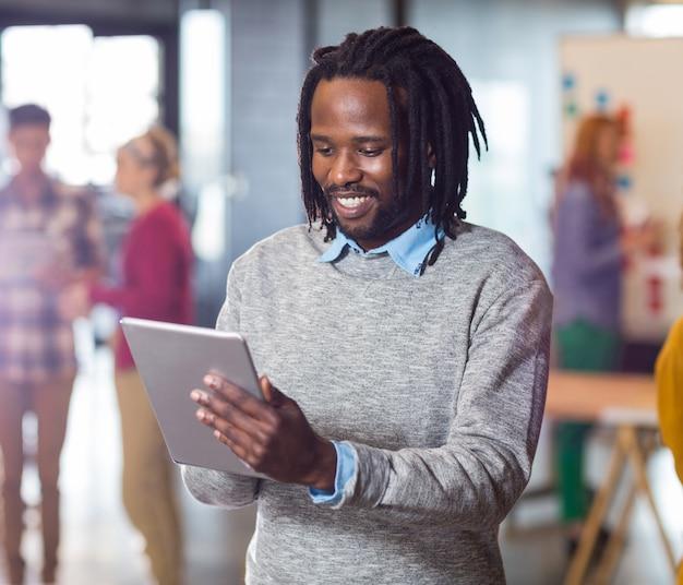 Mann mit digitaler tablette im büro