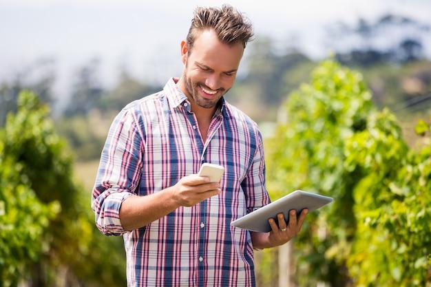 Mann mit digitaler tablette unter verwendung des handys am weinberg