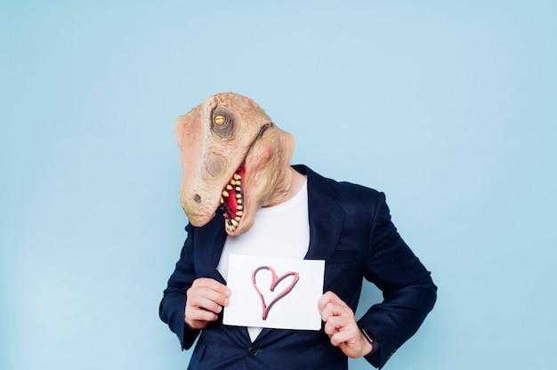 Mann mit dinosauriermaske hält ein schild mit herz