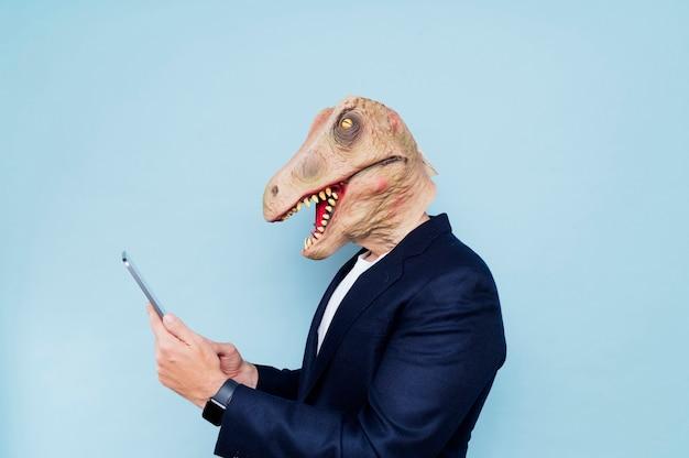 Mann mit dinosauriermaske.