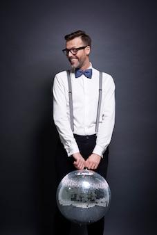 Mann mit discokugel posiert