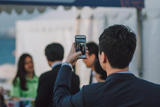 Mann mit dunklem haar, das leute auf smartphone fotografiert