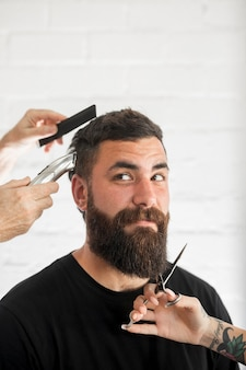 Mann mit dunklem haar und langem bart wird gepflegt und getrimmt