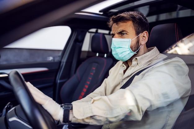 Mann mit e-maske und handschuhen, die ein auto fahren. infektionsprävention und seuchenbekämpfung. weltpandemie. bleib sicher.