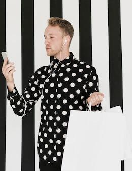 Mann mit eadphones und einkaufstaschen