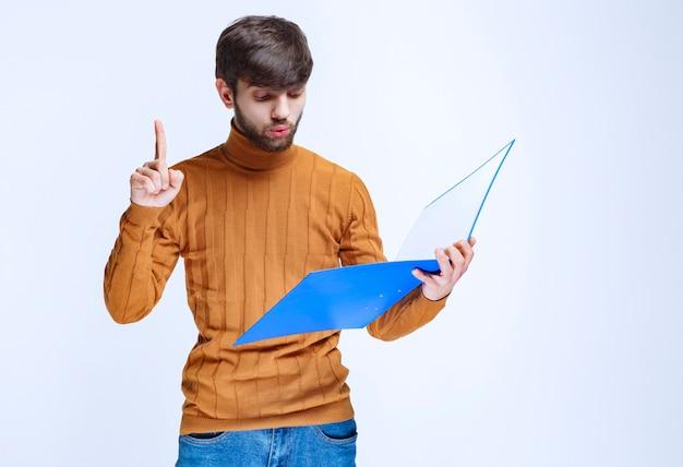 Mann mit einem blauen ordner, der den finger für aufmerksamkeit anhebt.
