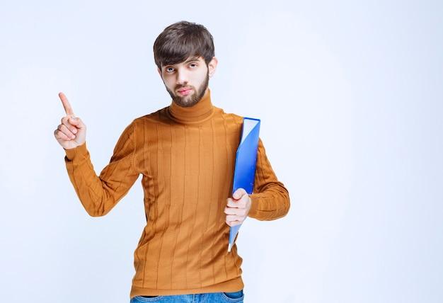 Mann mit einem blauen ordner, der die linke seite zeigt.