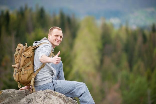 Mann mit einem braunen rucksack, der am rand eines felsens sitzt