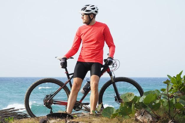 Mann mit einem fahrrad steht am ozeanufer