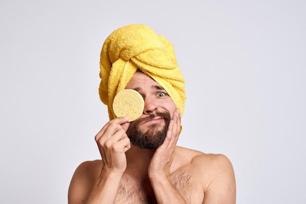 Mann mit einem gelben handtuch auf seinem kopf nackten schultern schwamm saubere haut gesichtspflege licht.