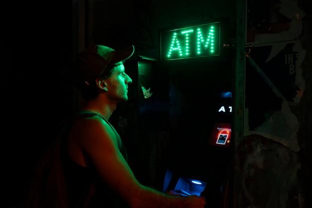 Mann mit einem geldautomaten für sein geld