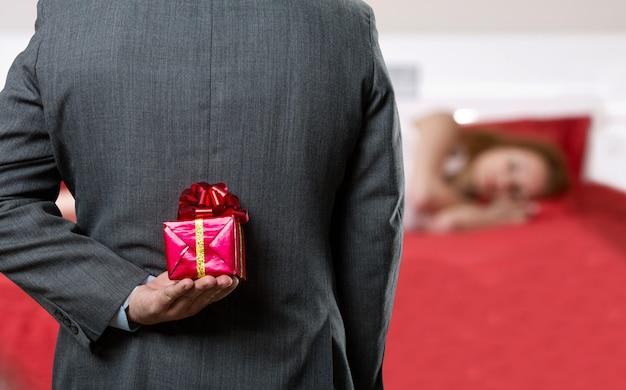 Mann mit einem geschenk hinter dem rücken