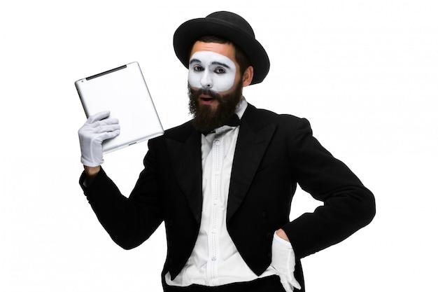 Mann mit einem gesichtspantomimen, der an einem laptop lokalisiert auf einem weiß arbeitet