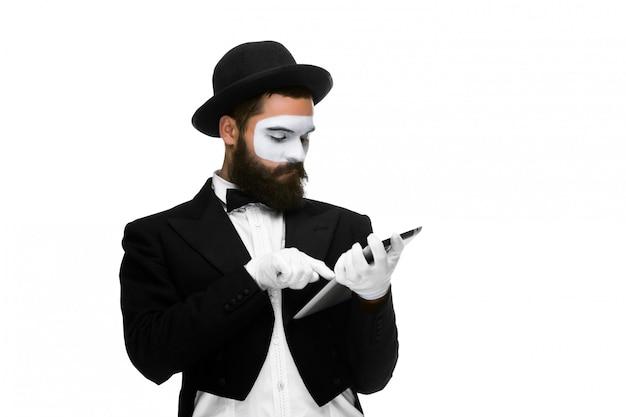 Mann mit einem gesichtspantomimen, der an laptop arbeitet