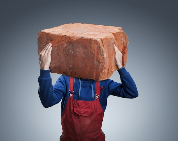 Mann mit einem großen ziegelstein in seinem kopf