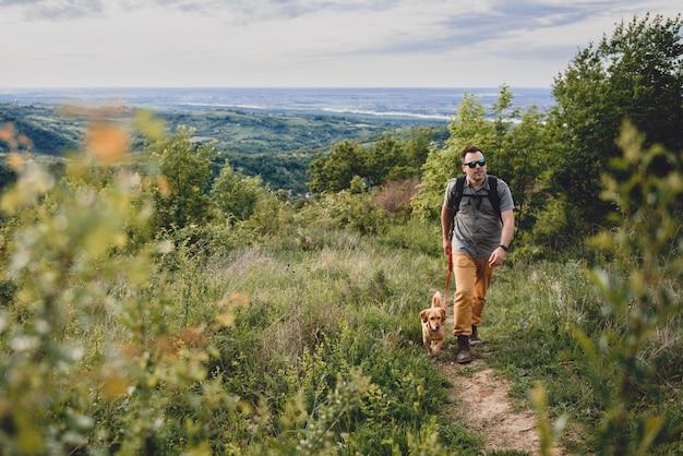 Mann mit einem hund, der entlang einen wanderweg geht