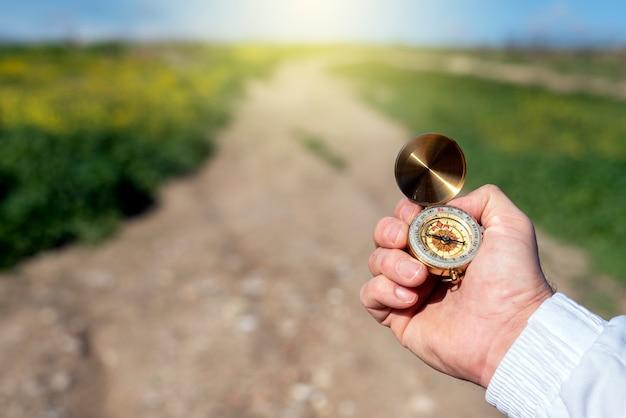 Mann mit einem kompass in einem feld