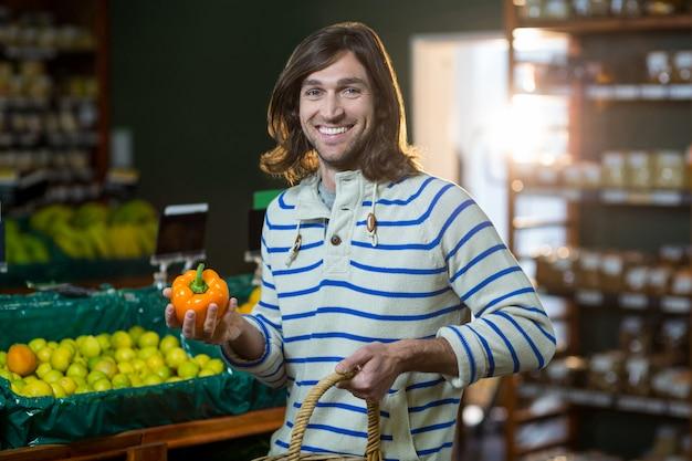 Mann mit einem korb, der paprika im organischen abschnitt auswählt