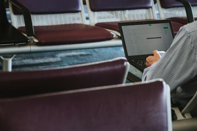 Mann mit einem laptop auf einem ledersitz im wartebereich am flughafen