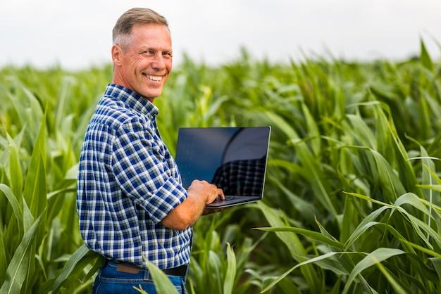 Mann mit einem laptop, der kamera betrachtet