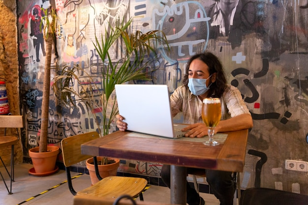 Mann mit einem laptop in einer modernen bar.