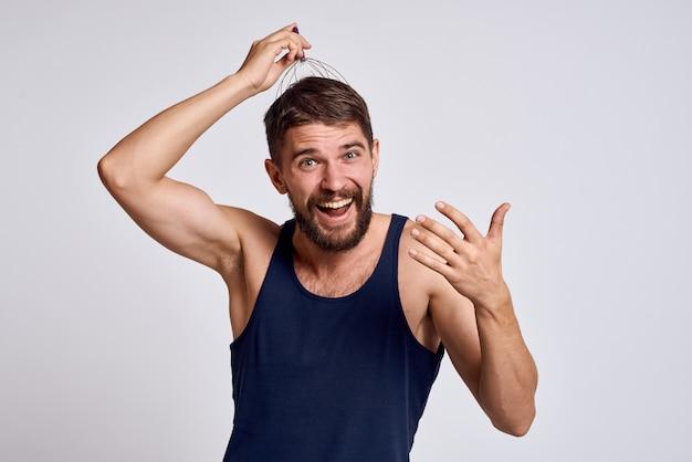 Mann mit einem massagegerät für den kopf und in einem blauen t-shirt auf einem leichten entspannenden bart emotionen